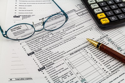 Tax documents with calculator and reading glasses on top